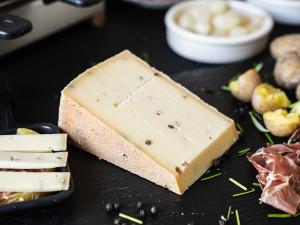 Raclette Käse aus Rohmilch mit buntem Pfeffer serviert beim Pfännchenraclette mit Beilagen