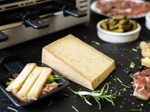 Stück Käse zum Raclette aus Rohmilch mit Kräutern für den Racletteofen serviert mit Beilagen